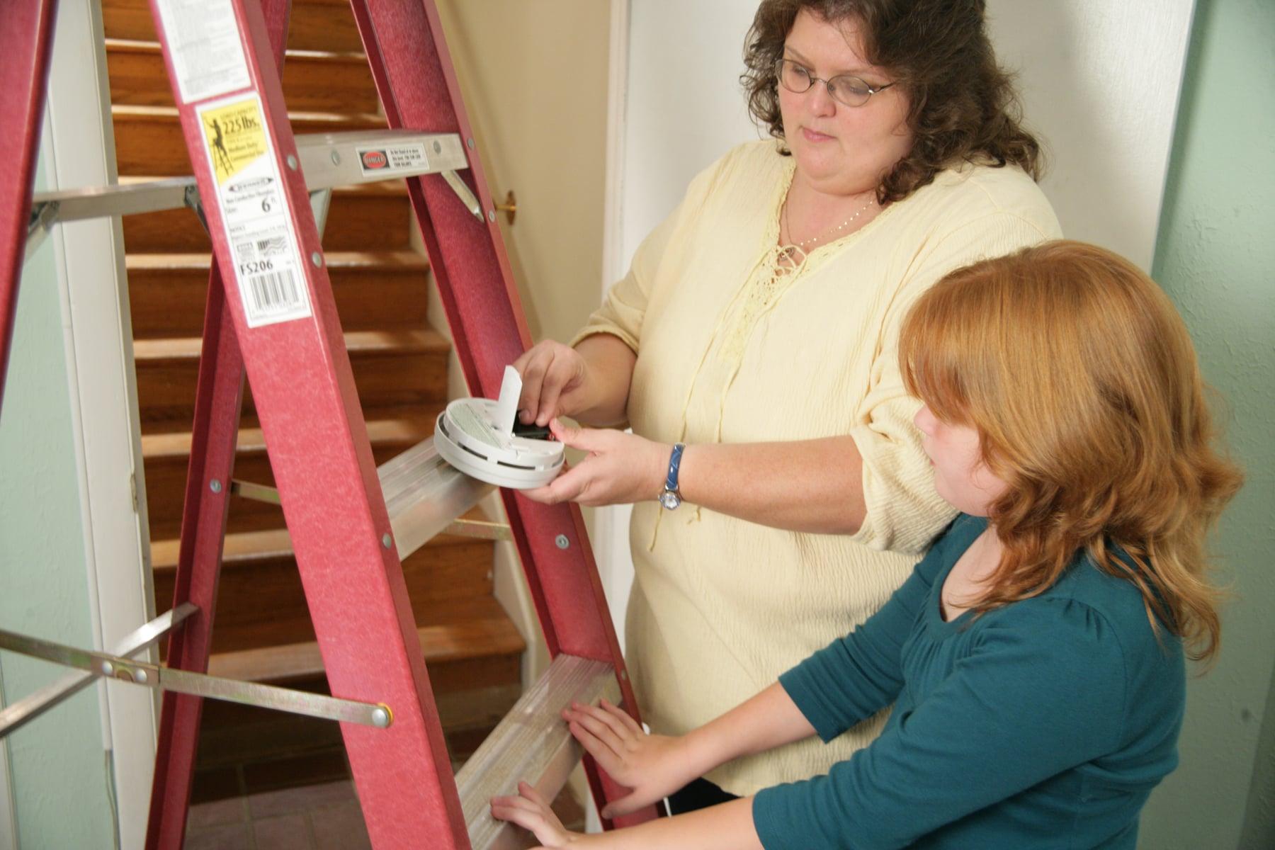 Woman Replacing Smoke Detector